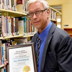 A photo of Jay Strickland with his Community Person in Literacy Award