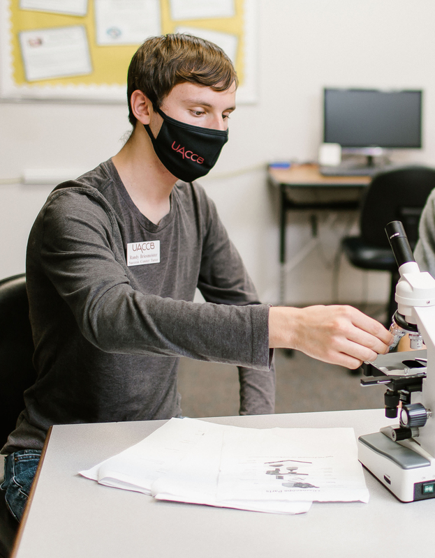 A photo of student Randy Briesmeister working with a microscope.