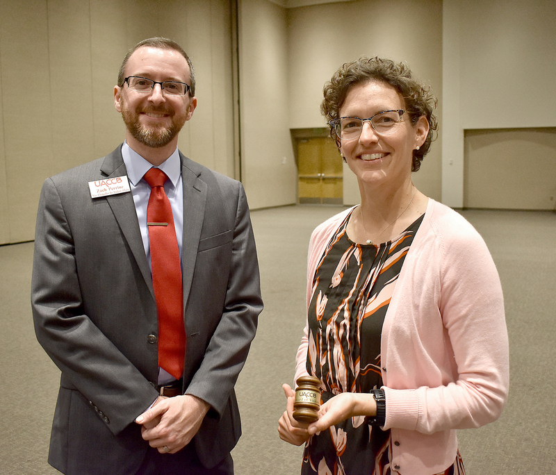 Zach Perrine presents Dr. Maggie Williams with the gavel during her final meeting with the UACCB board of visitors.